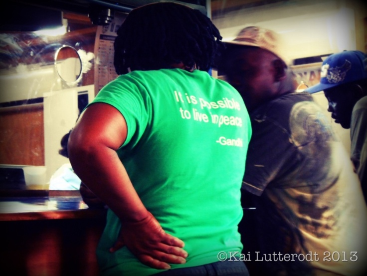 Haitian buisness woman orders her wholesale produce. The quote by Gandhi written on her t-shirt catches my eye