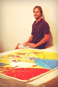 Dionisis sits by a colourful painting of various Orishas