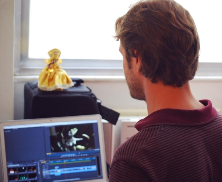 Editing one of his projects... An Orisha doll in a gold dress sits above his workstation