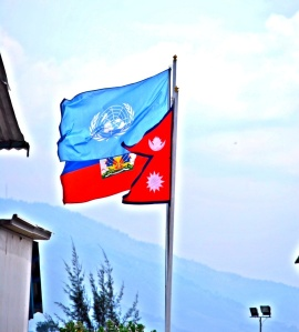 The Haitian, UN and Nepalese flag fly in unison